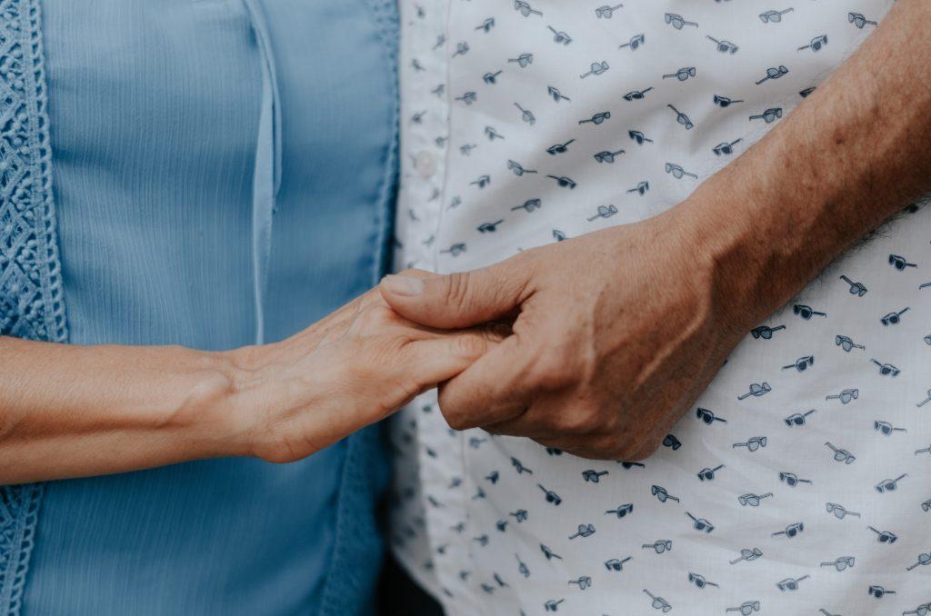 Lähikuva, jossa kaksi henkilöä pitää toistensa käsistä kiinni. Taustalla näkyy toisen sininen paita ja toisen henkilön valkoinen paita, jossa on pientä kuviota.